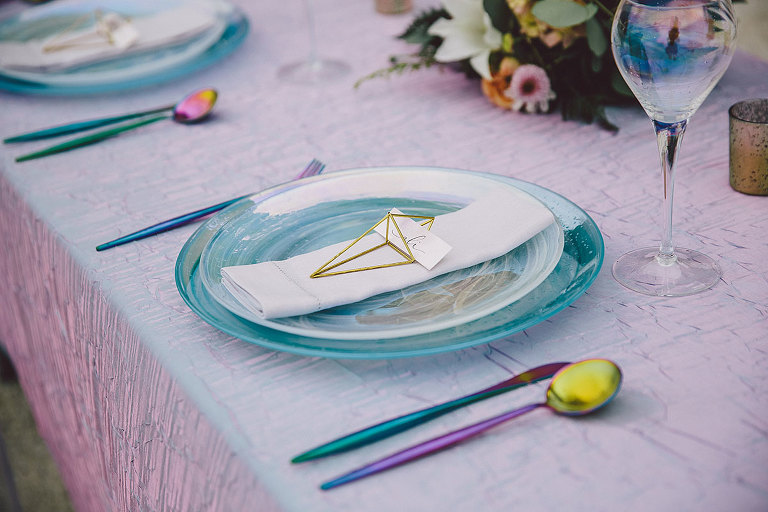 Shimmering opaline plates and iridescent cutlery on a purple table overlay create an appealing design for a modern seaside wedding design in Victoria BC - Party Mood
