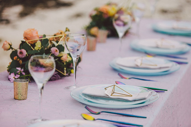 Iridescent tableware, shimmering blue plates, and floral accents with geometric elements frame this modern Victoria wedding design tablescape by Party Mood