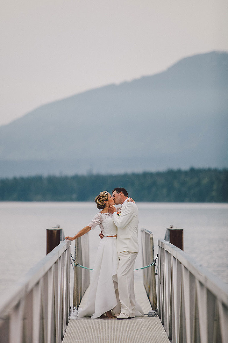Bride and groom stealing a kiss on a dock in a seaside wedding in Victoria BC styled by Party Mood.