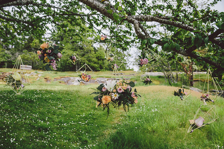 A display of several modern geometric wedding floral designs hanging from tree branches to style a beach wedding in Victoria BC styled by Party Mood.