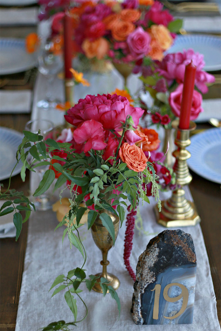 Brass candlesticks and a subtle, oatmeal hued linen table runner from the wedding decor rental inventory of Victoria BC wedding planner Party Mood offset the bold and bright florals of this tablescape design.