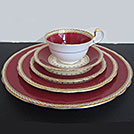 Vintage china in red with gold rimmed accents from the wedding decor rentals inventory of Party Mood.