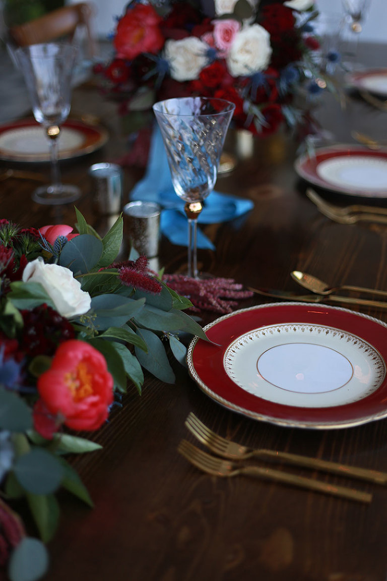 A luxurious table setting design in deep reds featuring plate settings and cutlery from the Party Mood wedding decor rental inventory.