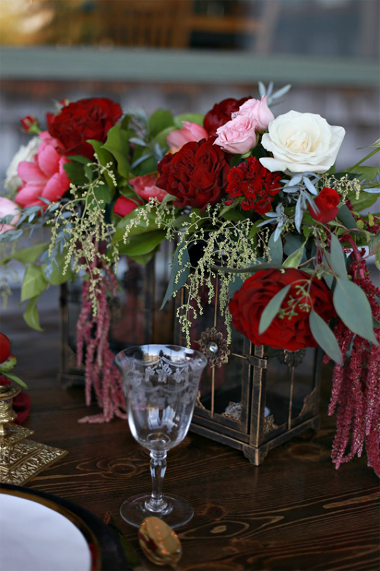 Beautiful wedding table stemware in front of a luxurious red wedding floral centerpiece styled by Party Mood.