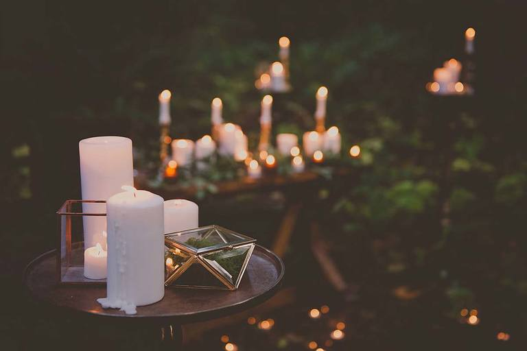 The warm glow of candlelight sets the scene for this forest themed outdoor wedding.