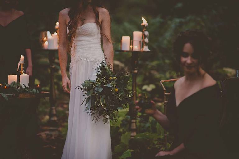 Bride holds a rustic styled bridal bouquet in front of tall candlesticks in a forest setting for a woodland inspired styled wedding shoot.