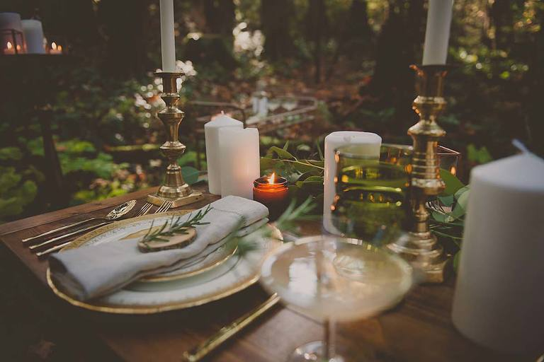 Rustic forest wedding tablescape featuring vintage china, vintage glassware, and brass candlesticks from the wedding decor rental inventory of Party Mood in Victoria BC