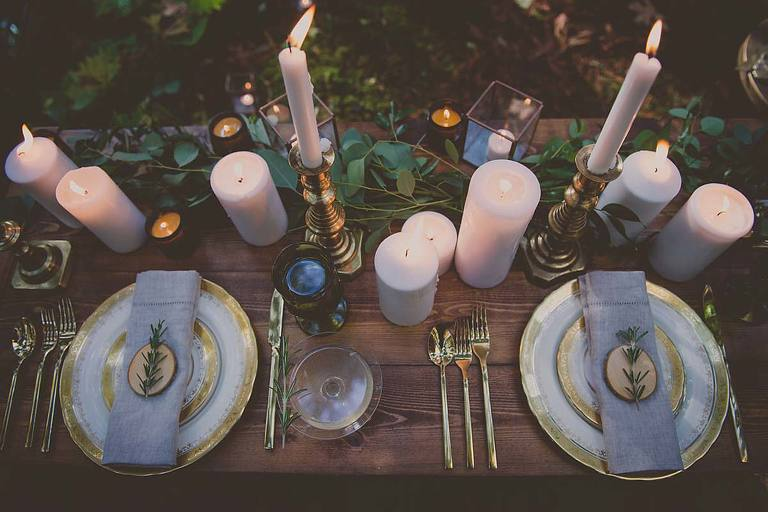 An overhead view of rustic woodland wedding decor items including; vintage china plates, vintage gold cutlery, vintage glassware, and brass candlesticks from the wedding decor rental inventory of Party Mood in Victoria, BC.